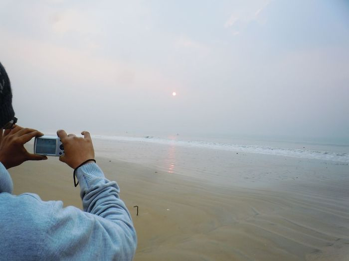 Cropped image of person photographing through camera at beach during sunset