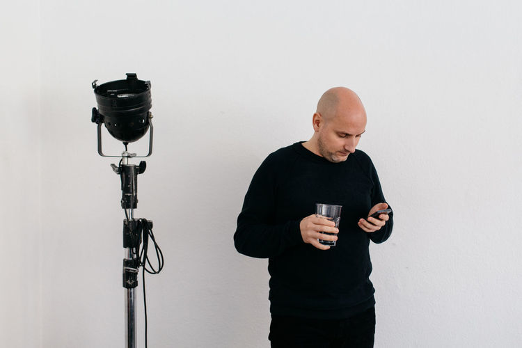 Studio Light Communication Contrast Day Drink Holding Men Mobile Phone One Man Only One Person People Shaved Head Standing Studio Shot Technology Using Phone Water Glass White Background White Wall Wireless Technology