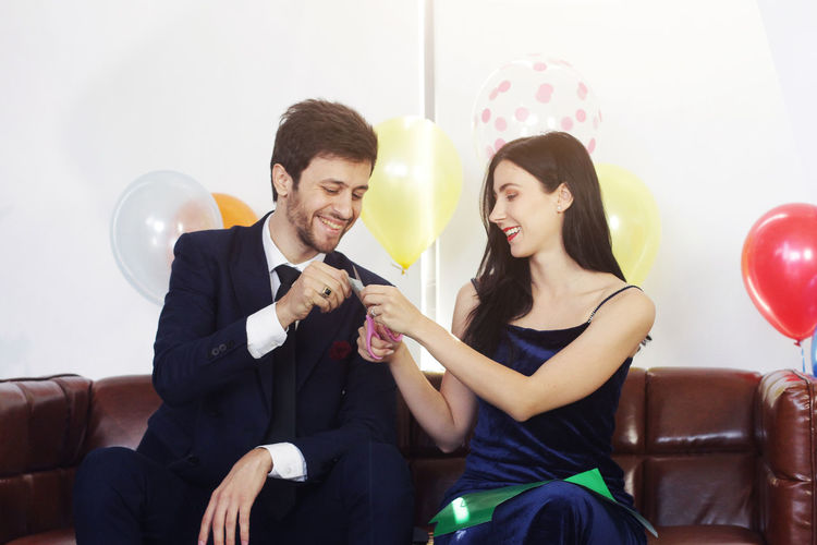 Young couple sitting on balloons
