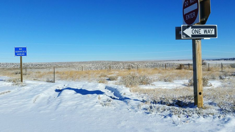 Road Sign On Snow Covered Field Against Clear Blue Sky