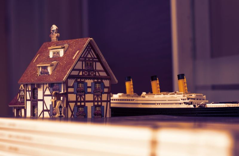 Close-Up Of Model House And Toy Ship On Table