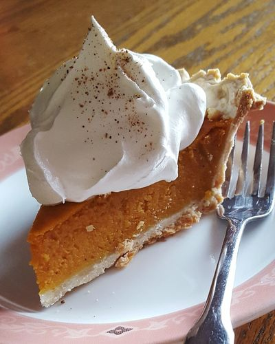 Close-up of pumpkin pie with whipped cream on plate