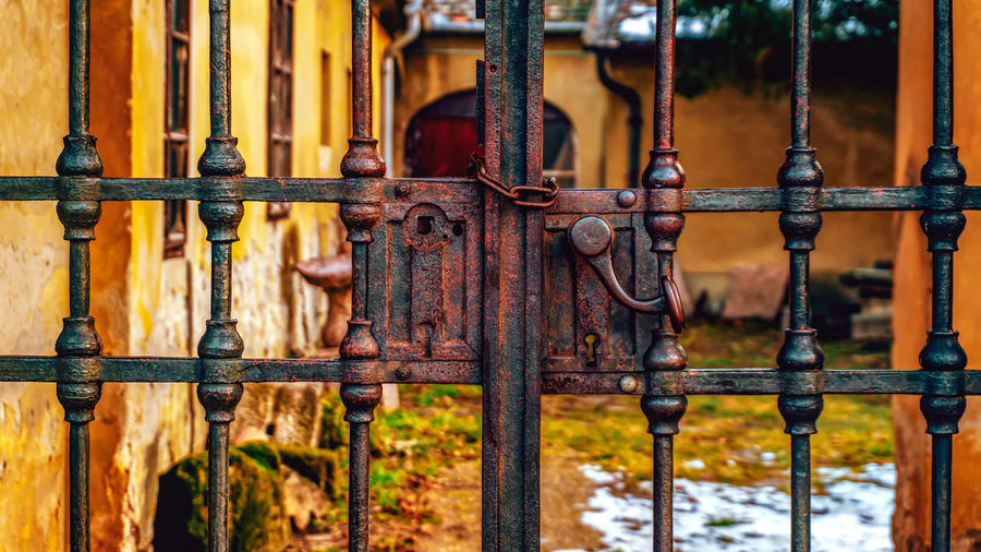 Close-up of rusty metal fence against old building