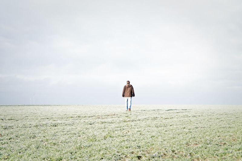 Rear View Of Man Walking On Grassy Field Against Sky