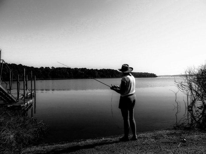 Woman fishing in lake against sky