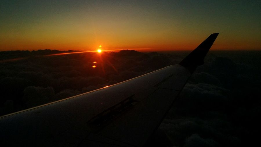 Airplane wing over landscape against sunset sky
