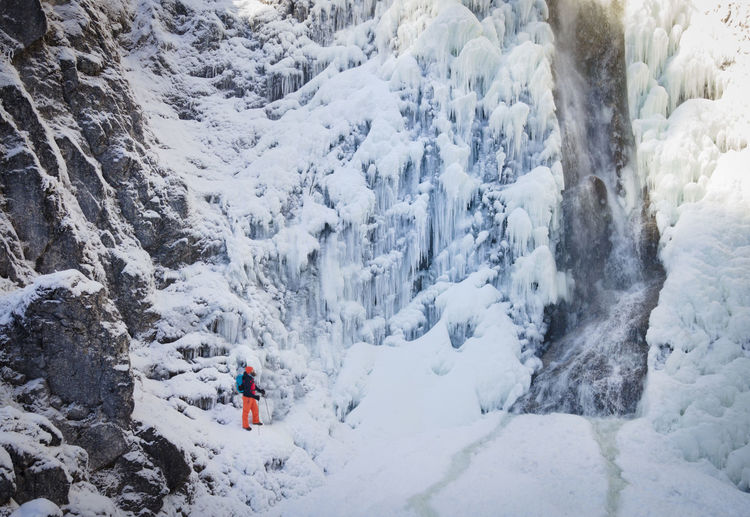 High angle view of man on snow covered mountains by waterfall during winter