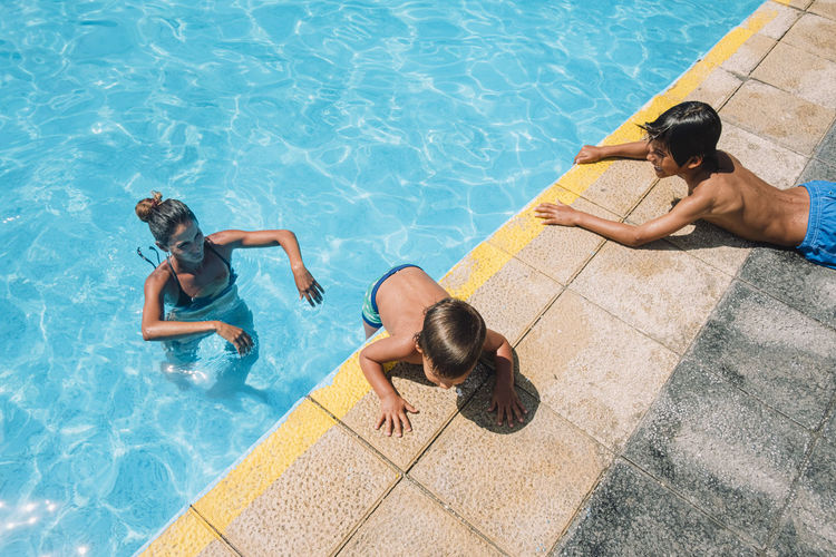 High angle view of friends lying on swimming pool