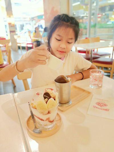 Girl having ice cream in restaurant