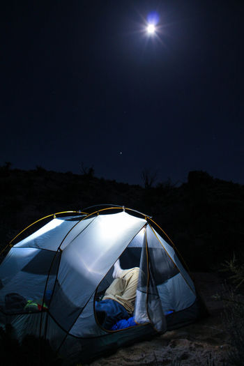 Man Resting In Illuminated Tent Against Sky At Night