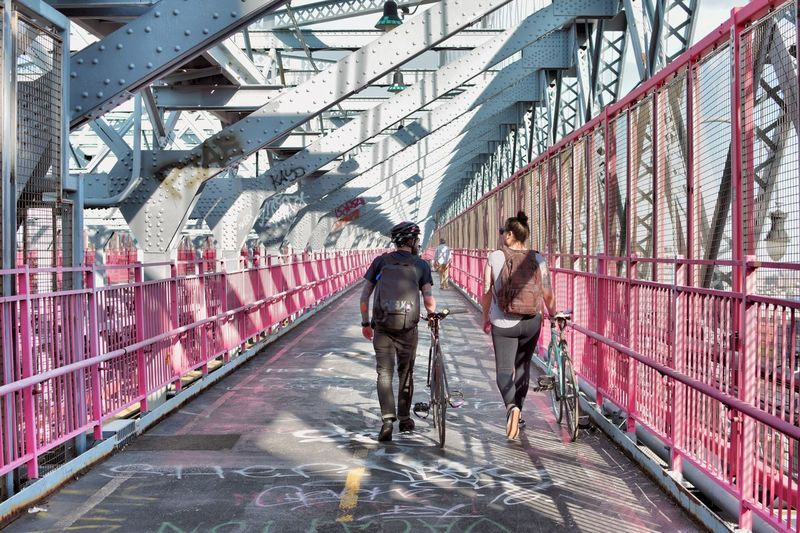 Rear view of friends with bicycles walking on bridge
