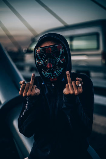 Portrait of man wearing mask gesturing outdoors