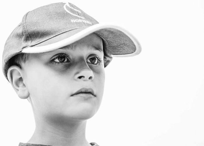 Close-up of boy wearing cap against white background