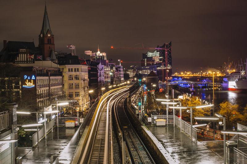 Illuminated railroad tracks in city against sky at night