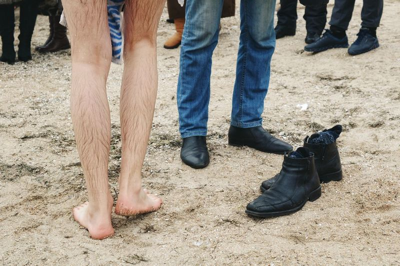 Human Leg Human Body Part Human Foot Outdoors Togetherness People Real People Sand Cold Wintertime Cold Day Epiphany Nature On Your Doorstep Aquatic Sport Azov Sea Motion Adventure Friendship Leisure Activity Man Sea Shoe Adults Only Standing Day