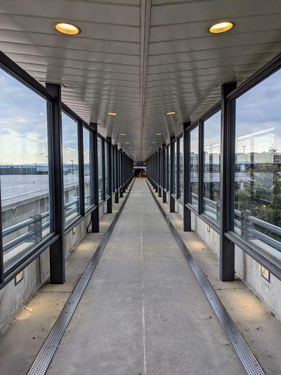 Illuminated railroad station platform seen through glass window