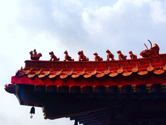 Low angle view of statues on temple roof against sky