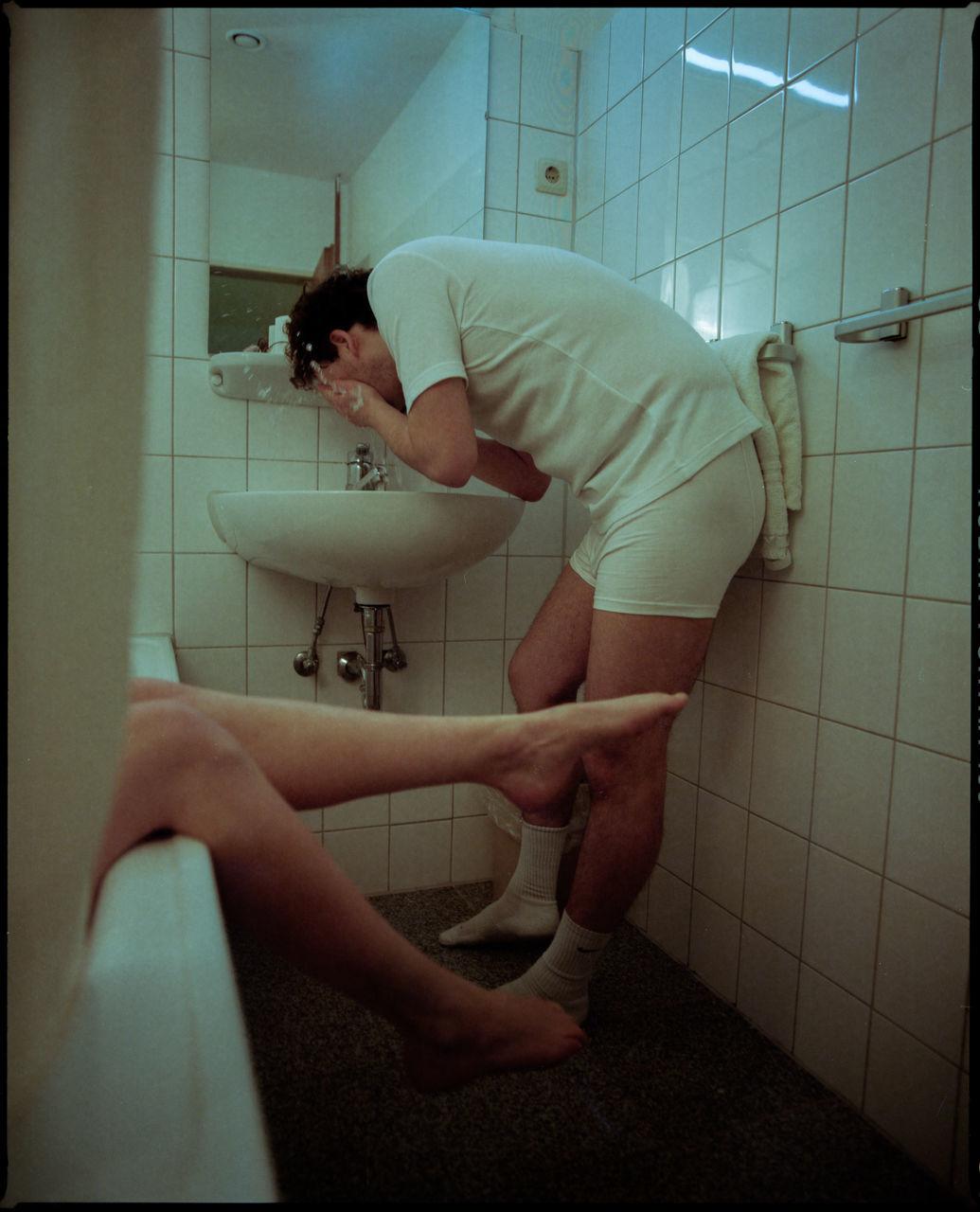 SIDE VIEW OF MAN IN BATHROOM