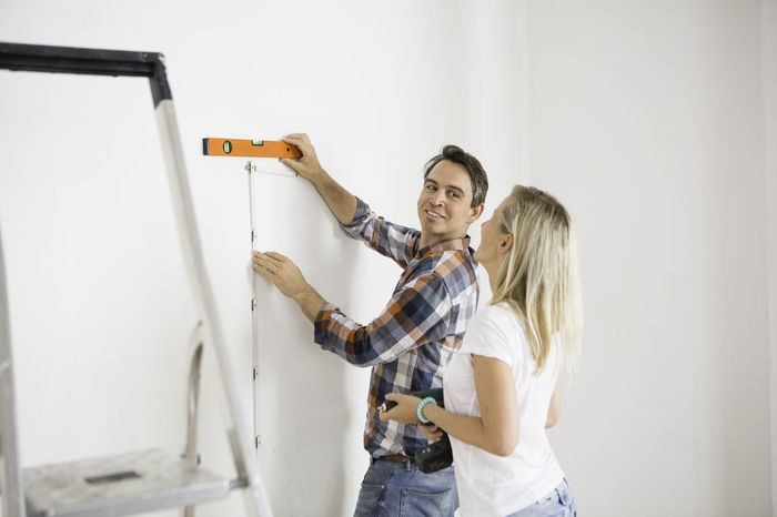 Young adults measuring a wall together Casual Clothing Front View Fun Happiness Ladder Leisure Activity Lifestyles Person Portrait Renovations Smile Three Quarter Length Toothy Smile Young Adult Young Women