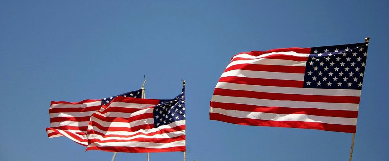 Low angle view of american flags against clear sky