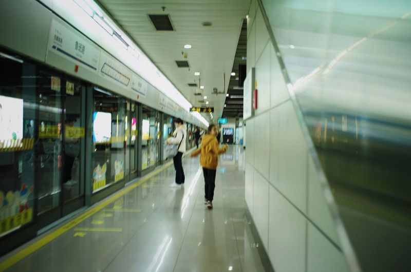Rear view of woman walking in subway station