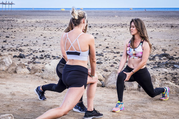 Female Friends Exercising At Beach