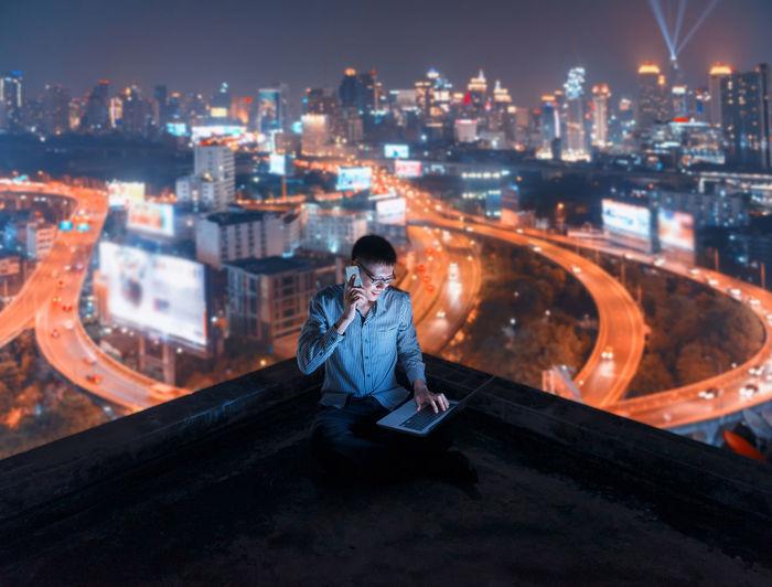 Man sitting in illuminated city against sky at night