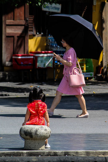 Rear view of women with pink umbrella on street