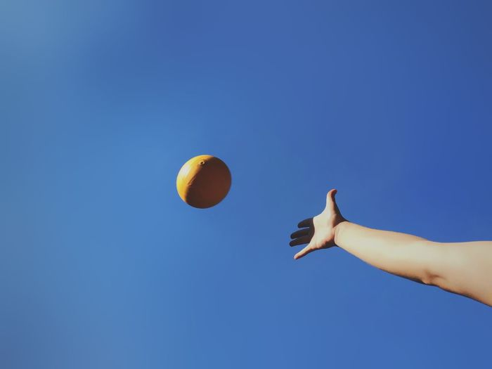 Low angle view of a hand throwing a yellow ball against blue sky