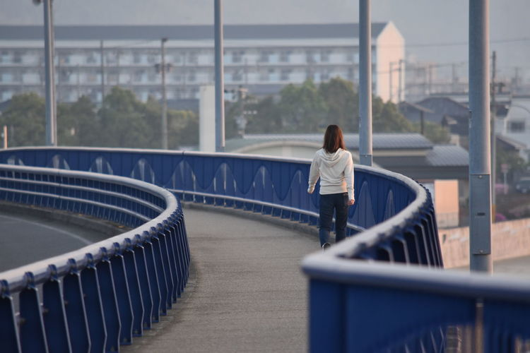 Rear view of woman walking on bridge against building