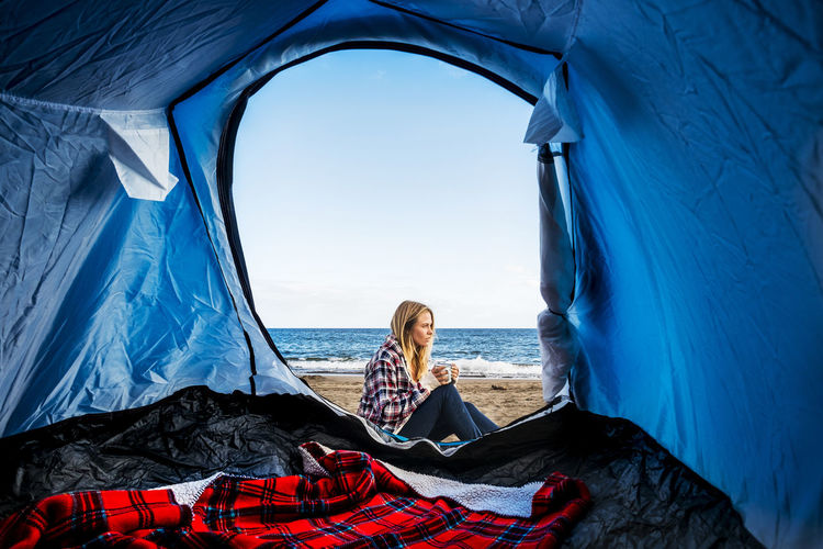 beautiful young girl camping on sand beach front to the ocean in Tenerife island Alone Freedom Adult Adventure Beach Campinglife Day Full Length Getting Away From It All Horizon Over Water Nature Ocean One Person One Woman Only Outdoors People Sea Sitting Sky Tenerife Island Tent Travel Vacations Women Young Adult