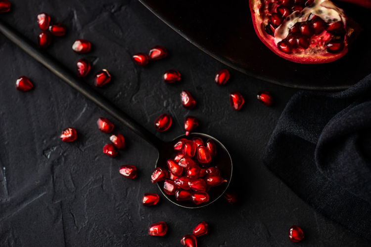 Organic pomegranate fruits with its seeds on black stone background