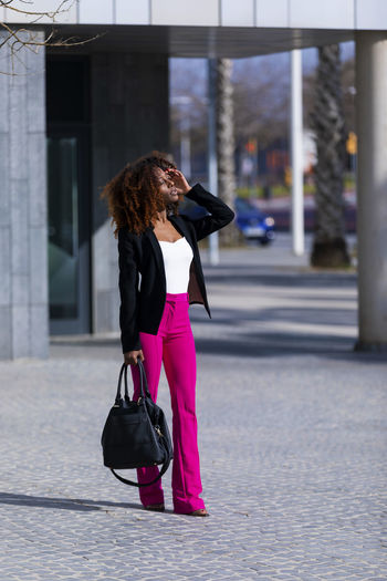 Front view of a young beautiful curly woman wearing elegant clothes and handbag while standing in the street in sunny day One Person Architecture Built Structure Building Exterior Real People Lifestyles City Women Bag Day Hair Full Length Standing Adult Young Women Focus On Foreground Leisure Activity Hairstyle Walking Outdoors Young Adult Woman African American Curly Hair Afro Denim Happiness Happy Fun Daylight Sunlight