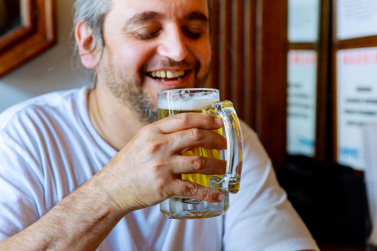 Smiling Man Drinking Beer At Home
