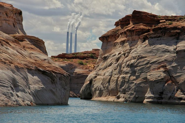 Rock formations at sea shore against smoke stacks