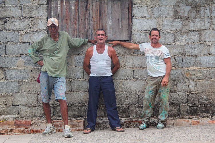Break Break From Work Brick Wall Casual Clothing Cienfuegos Cuba Day Front View Full Length Happiness Leisure Activity Lifestyles Men In Cuba Outdoors Painters Painters In Cuba Person Portrait Smiling Team Team Work Toothy Smile