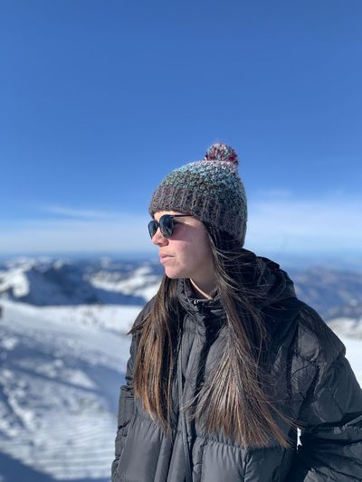 Young woman looking away while standing against sky during winter