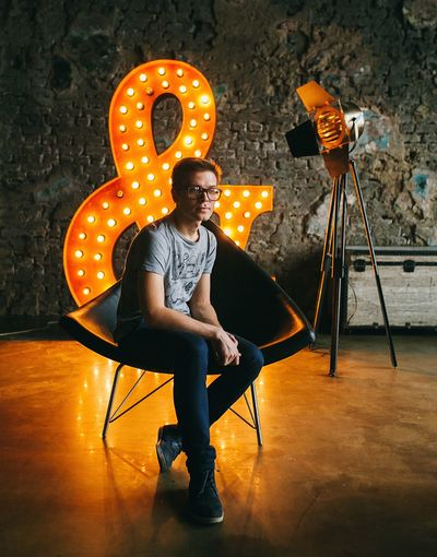 Young Man Sitting On Chair Against Wall With Illuminated Ampersand At Studio
