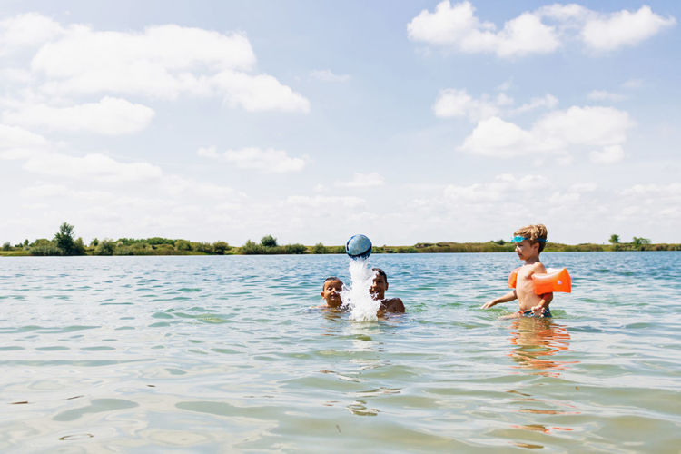 Boys playing with ball in sea against sky