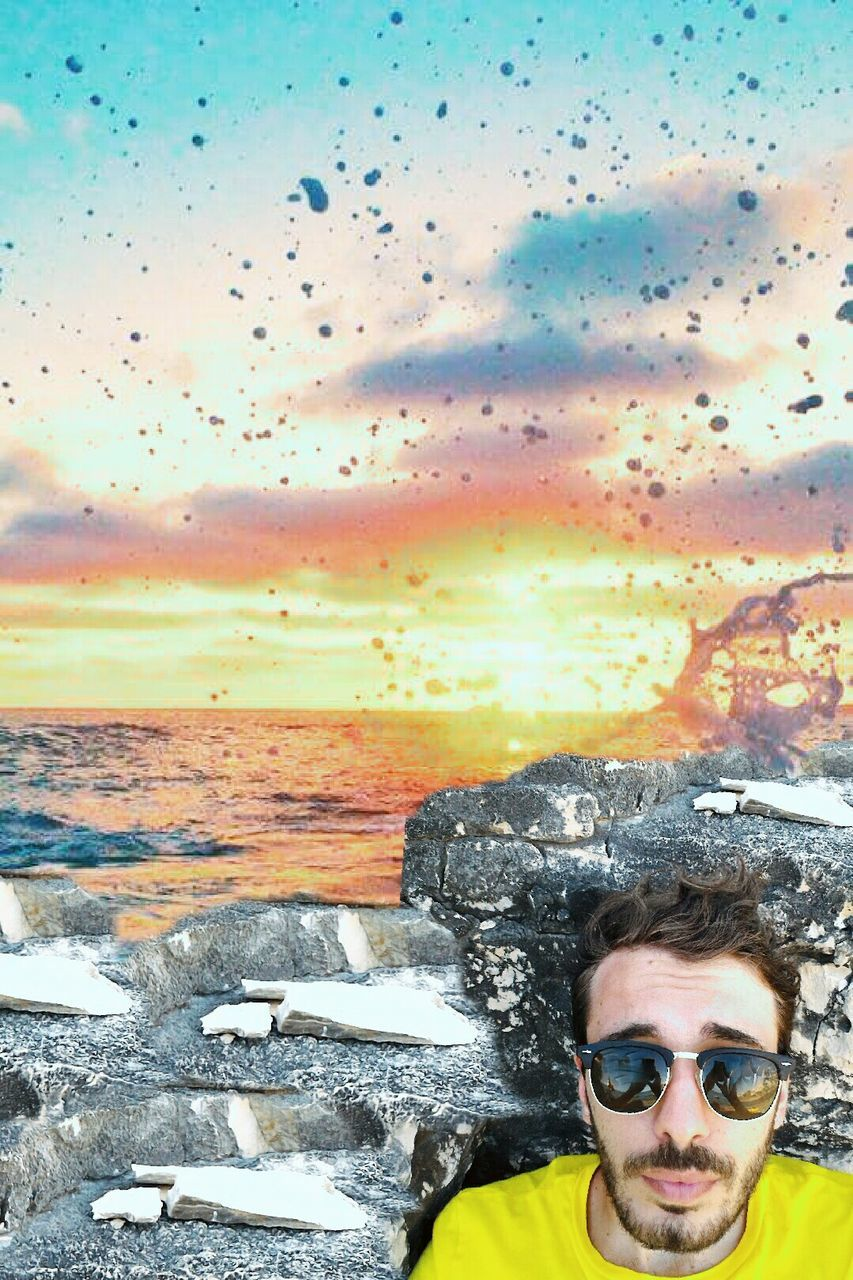 sunset, sunglasses, sky, nature, looking at camera, cloud - sky, front view, outdoors, sea, portrait, leisure activity, one person, beauty in nature, young adult, headshot, motion, water, activity, real people, lifestyles, scenics, landscape, multi colored, men, adult, day, one man only, people, adults only