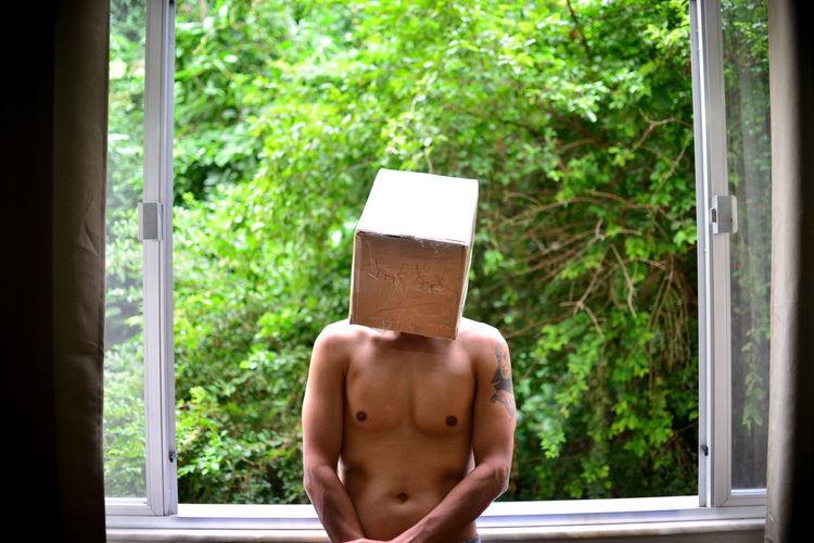 Shirtless Man Wearing Box While Standing Against Window