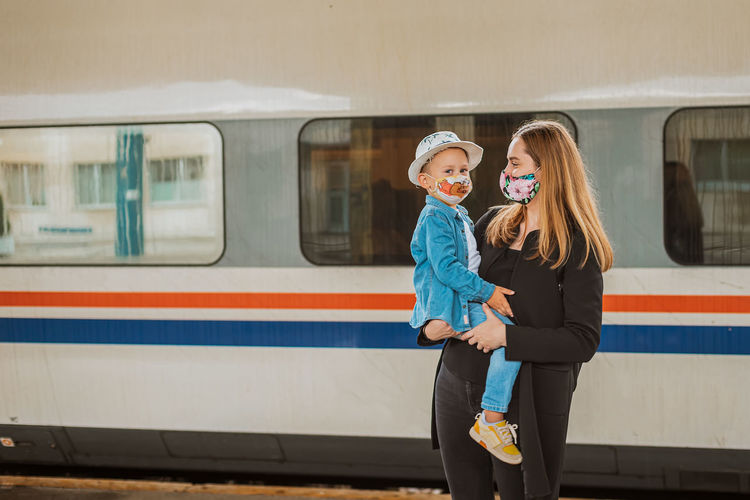 Mother looking while holding son at railroad station against train