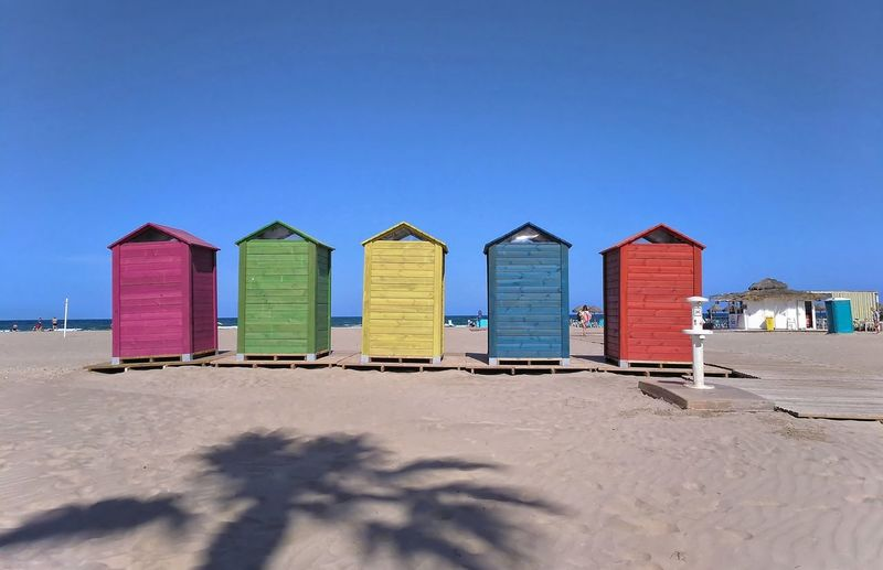 Small and colorful cabins to change clothes placed on the beach of my city, functional but also attractive urban furniture, designed to give visual pleasure at the same time as a practical service for beach users Beach Sand Sky Hut Water Sea Building Outdoors Landscape House Summer Coast No Person Outdoor Nature Blue Small Housing Travel Countryside Portable Toilet Large Cart Seashore Restroom Cabin Reside Vacation Shelter Daylight Covered Shack Architecture Barn Outhouse Dune Colorful Empty Drawn Leisure Man Shoreline Sun White Fair Weather València Vlc SPAIN Filigranasdigitales Built Structure