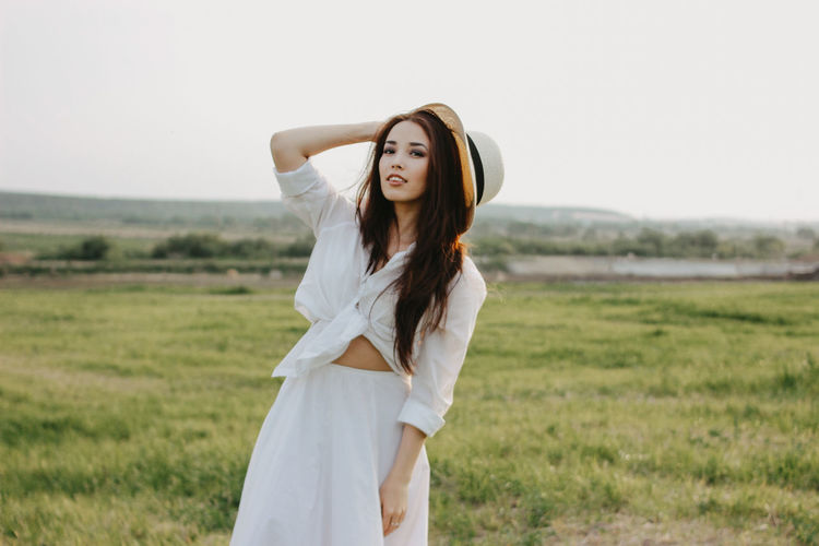 Portrait of smiling beautiful woman wearing sun hat standing on grassy land