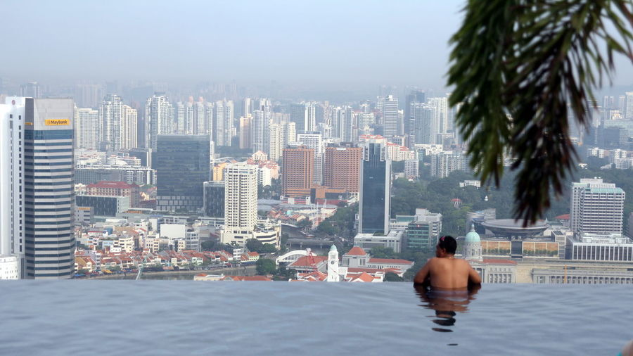Rear view of shirtless man looking at cityscape while swimming in infinity pool