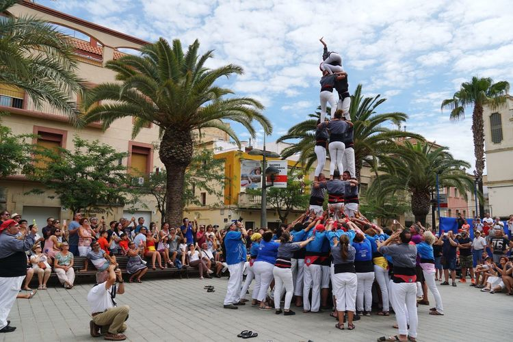 human castles of catalonia First Eyeem Photo Eye4photography  Castellers Colaboration Popular Tradition Human Castles Catalonia Is Not Spain Catalunya Catalonia Togetherness Culture Human Condition Tree Palm Tree Statue Men City Sky Festival Ceremony Traditional Culture