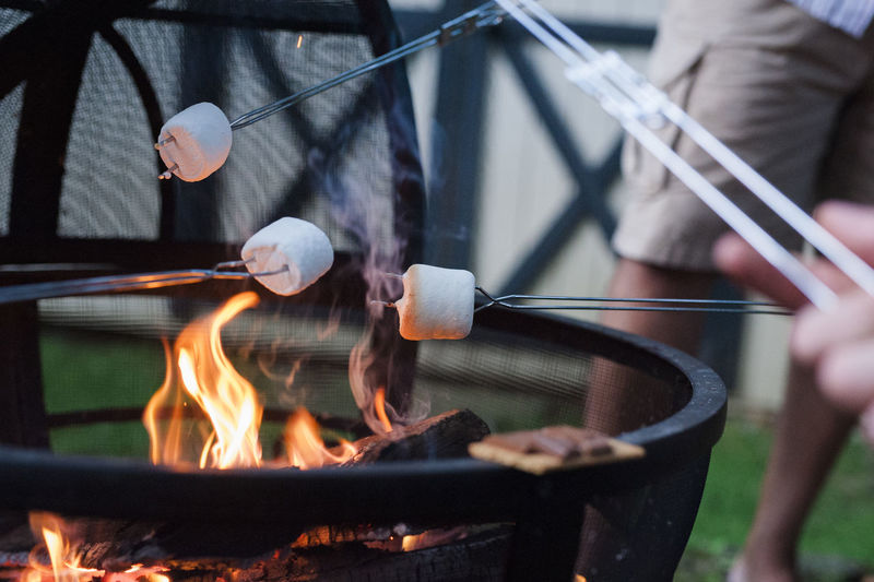Close-up of hands on barbecue grill