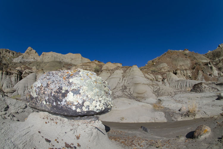 Panoramic view of rocks against clear blue sky