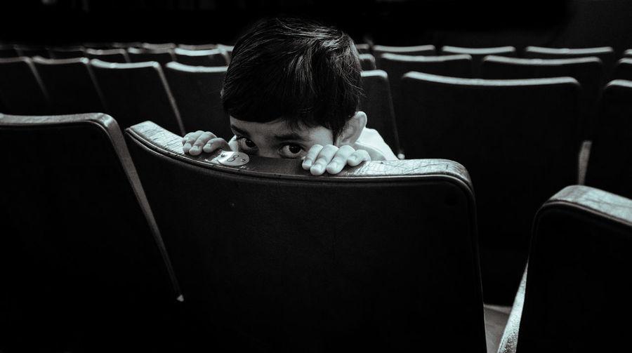 Portrait of boy hiding on chair