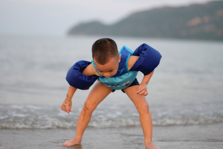 Boy Wearing Water Wings While Playing On Shore At Beach